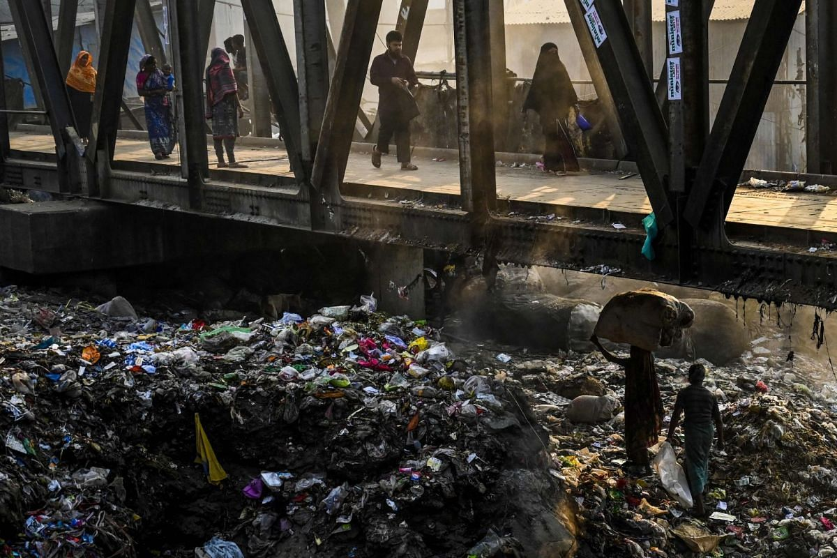 A Bangladeshi woman (lower right) carries recyclable waste over piles of trash underneath a pedestrian bridge in Dhaka, on Jan 23, 2019.