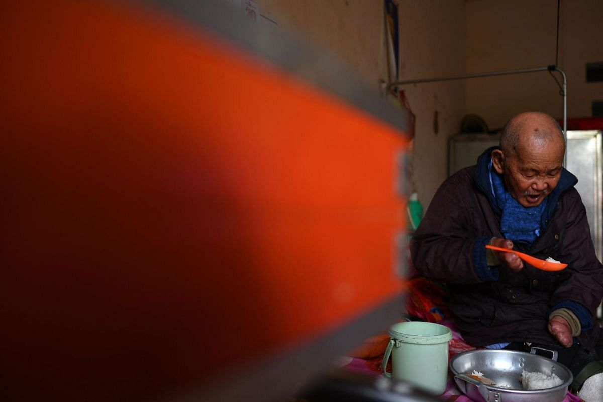 Leprosy survivor Nguyen Quang Chieu, 85, eats his lunch inside his room at the hospice.