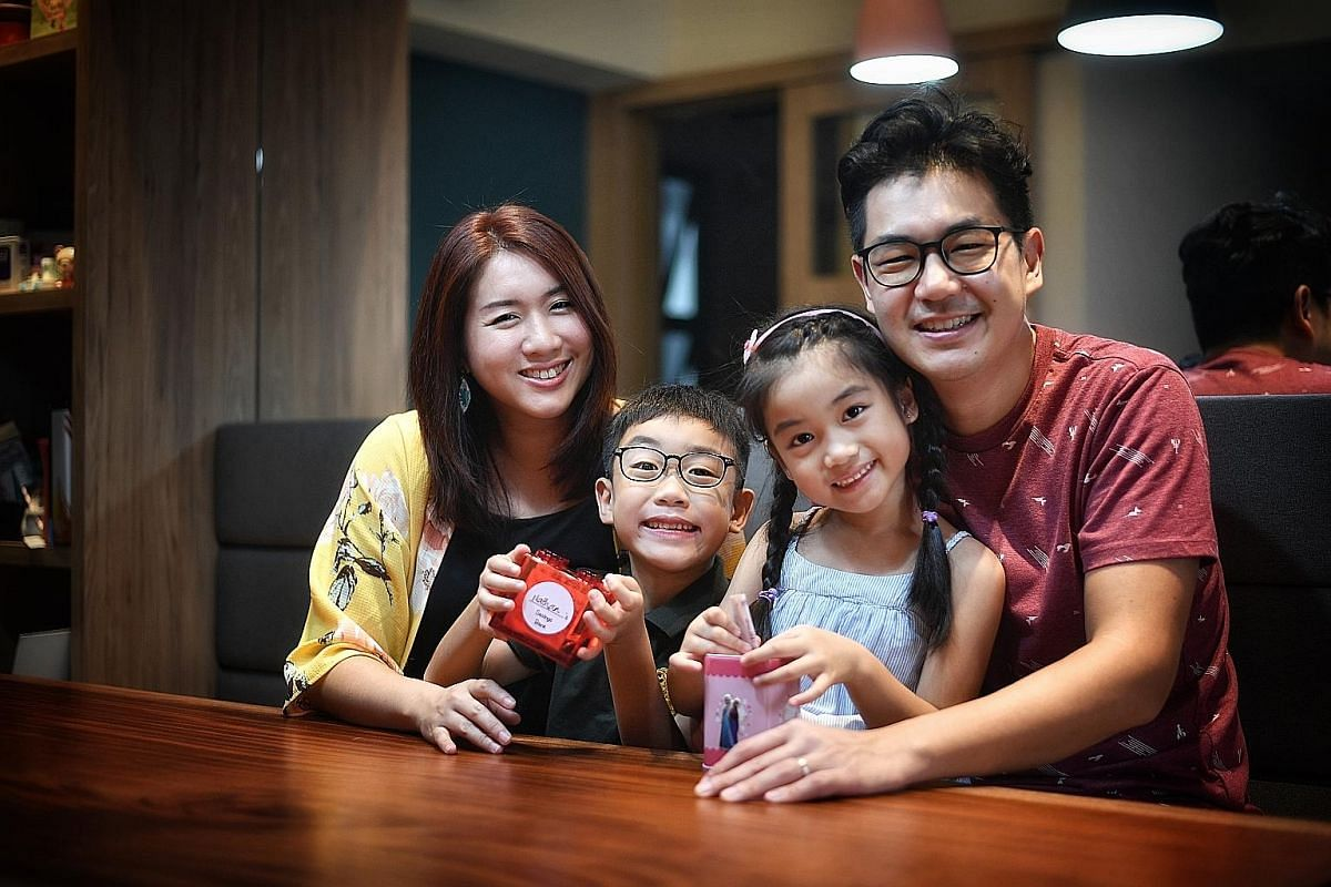 Ms Esther Tan (left) and her husband, Mr Elvin Foong, allow their children Nathan and Phoebe to use three $2 notes from their hongbao collection to shop at $2 store Daiso. Ms Angeline Wee (second from left) uses The Game Of Life board game to teach d