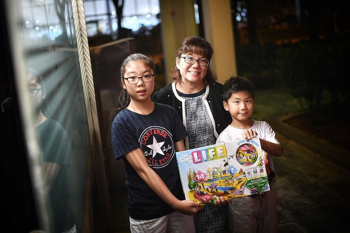Ms Angeline Wee (second from left) uses The Game Of Life board game to teach daughter Janelle and son Noel about financial issues.