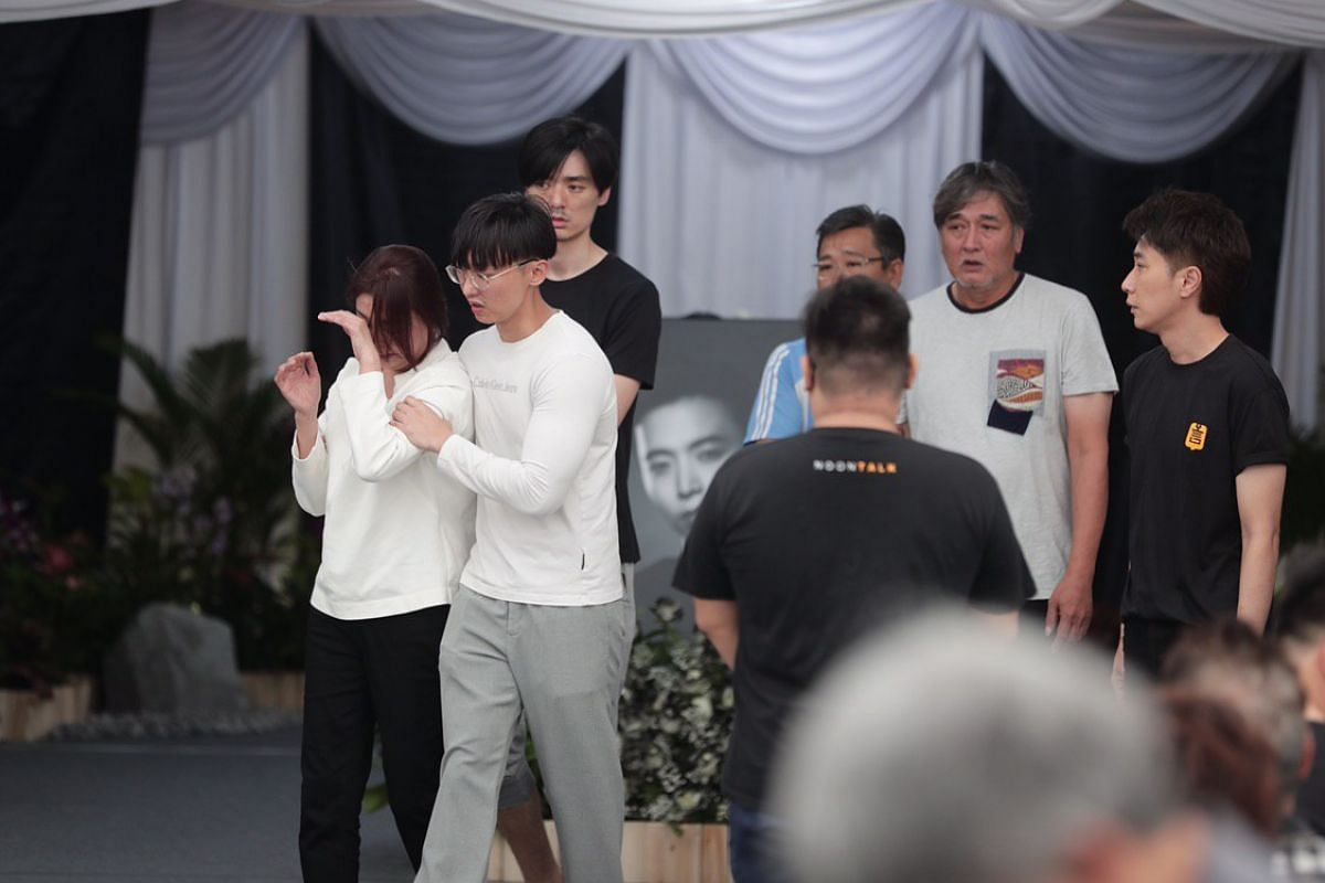 Aloysius Pang's mother (left), supported by her sons Jefferson (in white) and Kenny (black), and her husband (second from right), together with Aloysius' manager Dasmond Koh (right) greiving during the wake service.