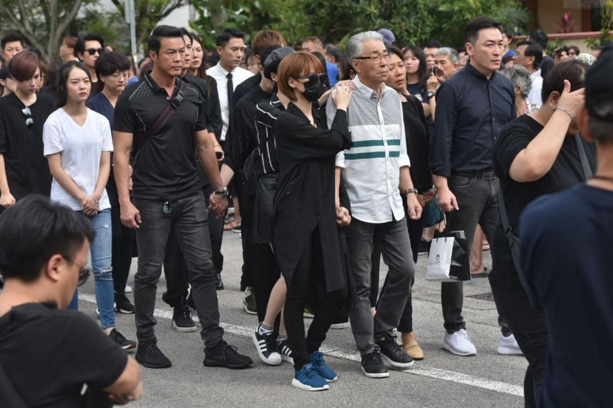 Actress Jayley Woo (in mask), the girlfriend of Aloysius Pang, and actor Chen Shucheng (in grey), together with actors Zheng Geping (left) and Rayson Tan (right) following the hearse of Aloysius Pang, on Jan 27, 2019.