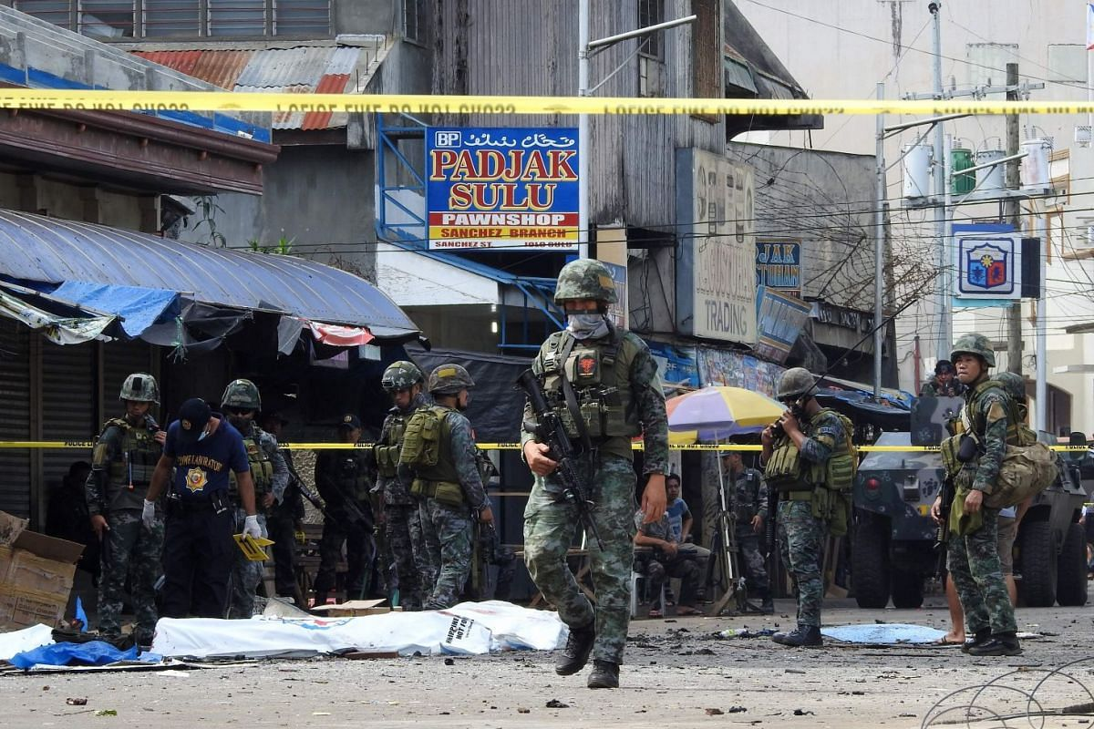 Policemen and soldiers keep watch as body bags (in white), containing the remains of blast victims, are seen in a cordoned area outside a church in Jolo, Sulu province on the southern island of Mindanao, on January 27, 2019. PHOTO: AFP