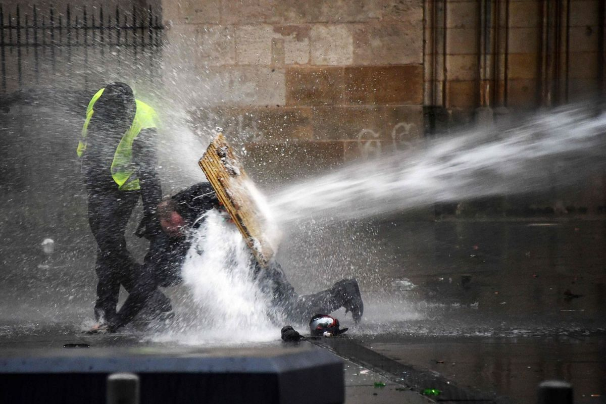 "Protesters protect themselves from water cannon during an anti-government demonstration called by the Yellow Vests ""Gilets Jaunes"" movement on January 26, 2019 in Bordeaux. PHOTO: AFP"