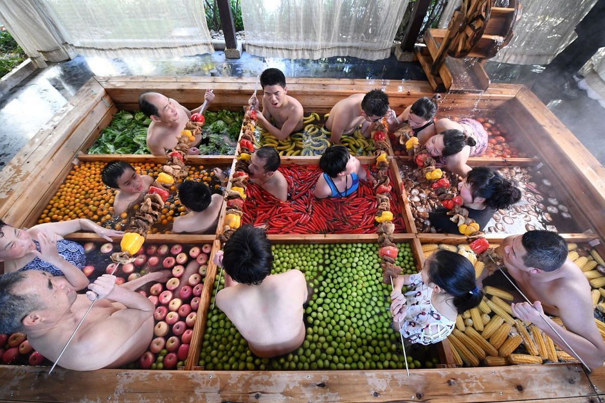 People enjoy a barbecue as they bath in a hotpot-shaped hot spring filled with fruits and vegetables, at hotel in Hangzhou, Zhejiang province, China January 27, 2019. PHOTO: REUTERS