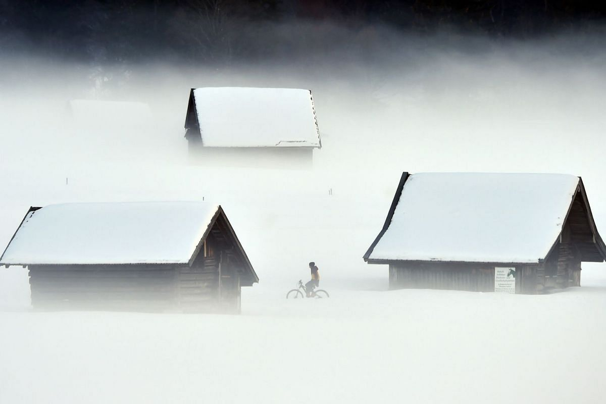 A cyclist passes a snowy meadow way during foggy winter weather with temperatures by the freezing point in Garmisch-Partenkirchen, southern Germany, on January 27, 2019. PHOTO: AFP