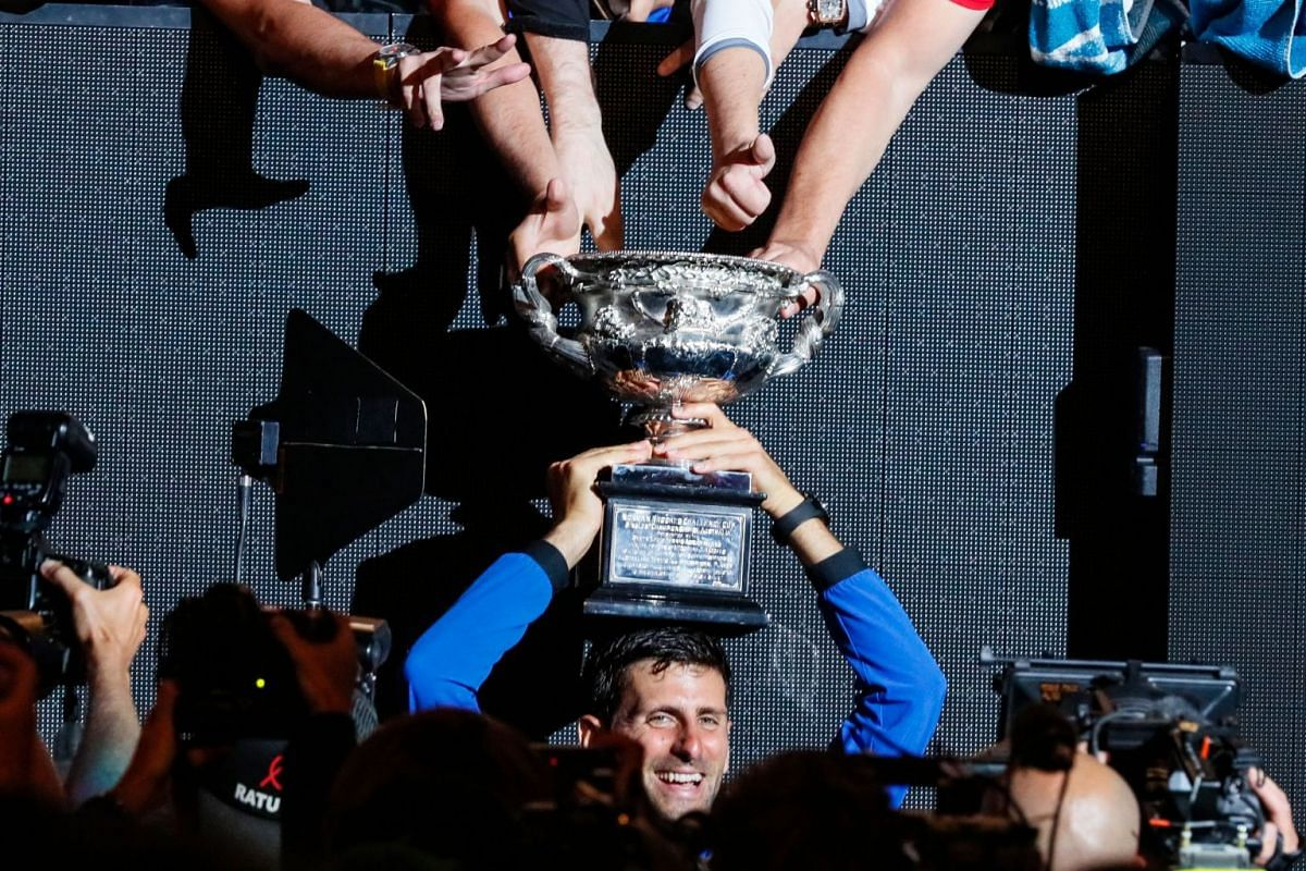 Serbia's Novak Djokovic celebrates with the championship trophy during the presentation ceremony after his victory against Spain's Rafael Nadal in the men's singles final on day 14 of the Australian Open tennis tournament in Melbourne on January 27,