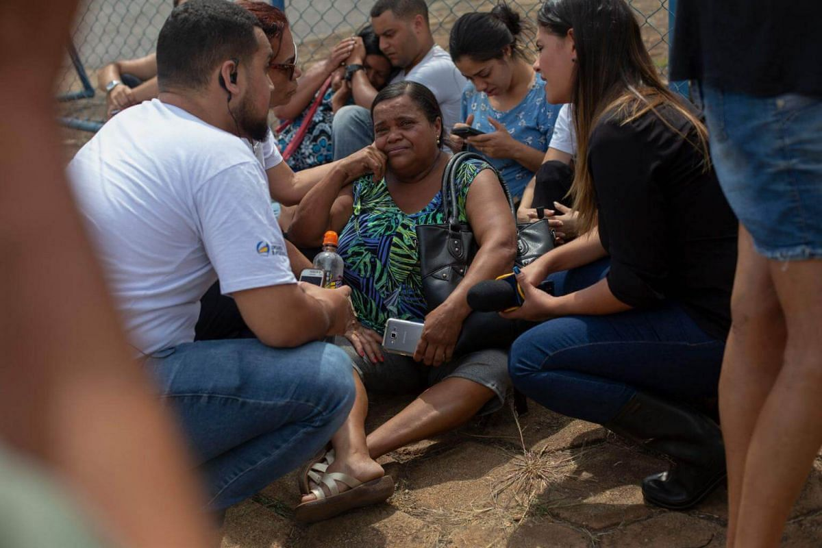People wait for information about their family members in front of the Crisis Command Centre organised by the Minas Gerais government in the town of Brumadinho, on Jan 26, 2019.