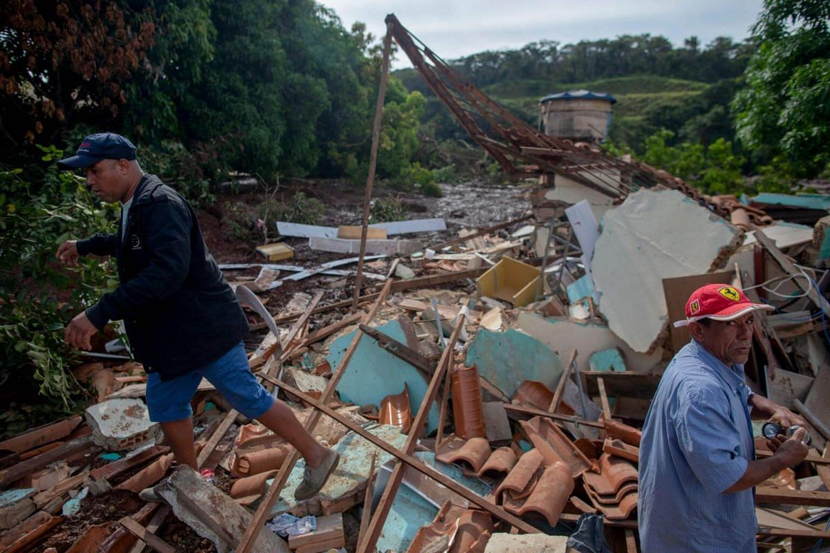 People from the community of Parque da Cachoeira navigate over debris after the collapse of a dam near the town of Brumadinho, on Jan 26, 2019.