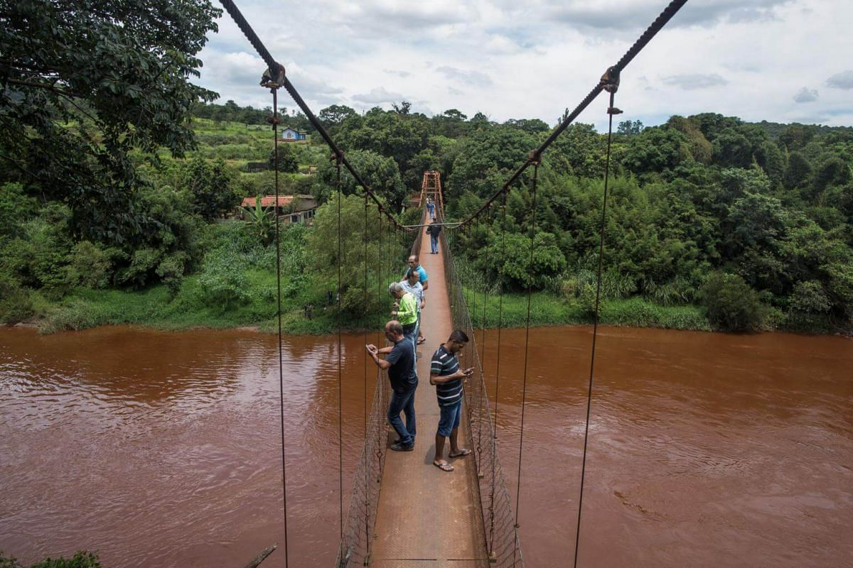 Residents stand on a bridge over flood waters after a dam burst in Brumadinho, Minas Gerais state, on Jan 27, 2019.