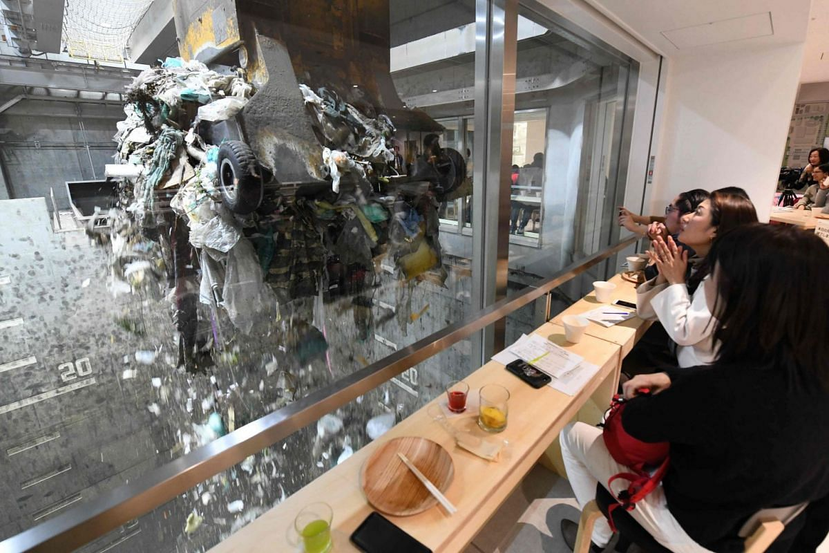 """A photo released on January 29, 2019,  shows customers watching an enormous crane pick up rubbish for incineration at a combustible waste pit while having a drink and snack at the """"Gomi (trash) Pit"""" bar in Tokyo on January 18, 2019. PHOTO: AFP"""