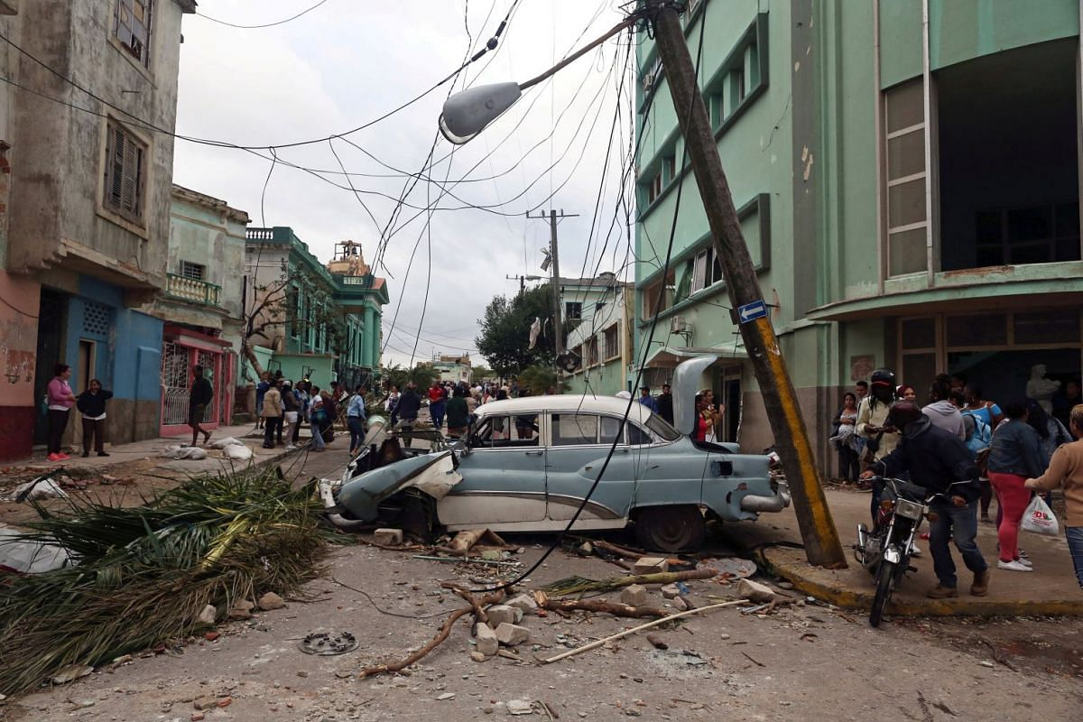 People walk past debris after a tornado ripped through a neighbourhood in Havana, Cuba January 28, 2019. PHOTO: REUTERS