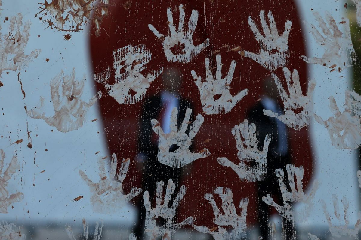 Security guards of Brazilian mining company Vale SA are seen through hand prints made from mud during a protest in front of Vale SA headquarters in Rio de Janeiro, Brazil January 28, 2019. PHOTO: REUTERS