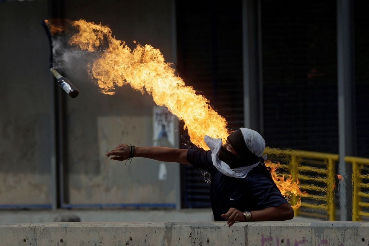 A demonstrator throws a petrol bomb towards policemen (not pictured) during a protest against Honduras' President Juan Orlando Hernandez outside the National Autonomous University of Honduras (UNAH) in Tegucigalpa, Honduras January 28, 2019. PHOTO: R