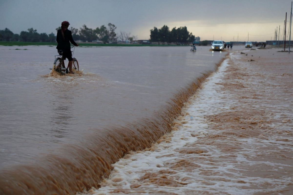 A man rides his bicycle on a flooded street after heavy rainfall on the outskirt of Najaf, Iraq January 28, 2019. PHOTO: REUTERS