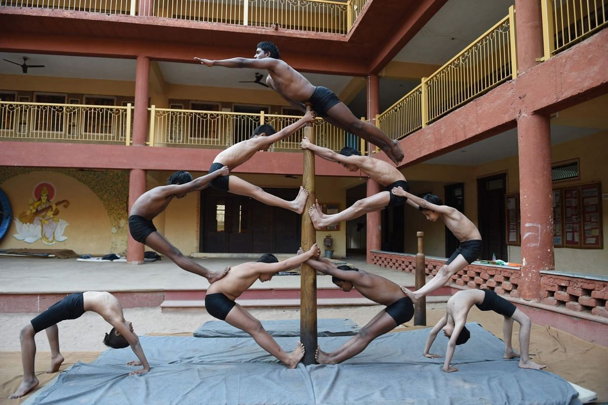 Gymnasts practise the traditional Mallakhamba sport with a pole, in Ahmedabad on January 28, 2019. PHOTO: AFP