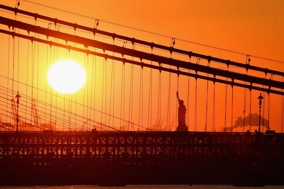 The sun sets next to the Statue of Liberty seen through the Brooklyn Bridge on January 28, 2019 in New York City. PHOTO: AFP