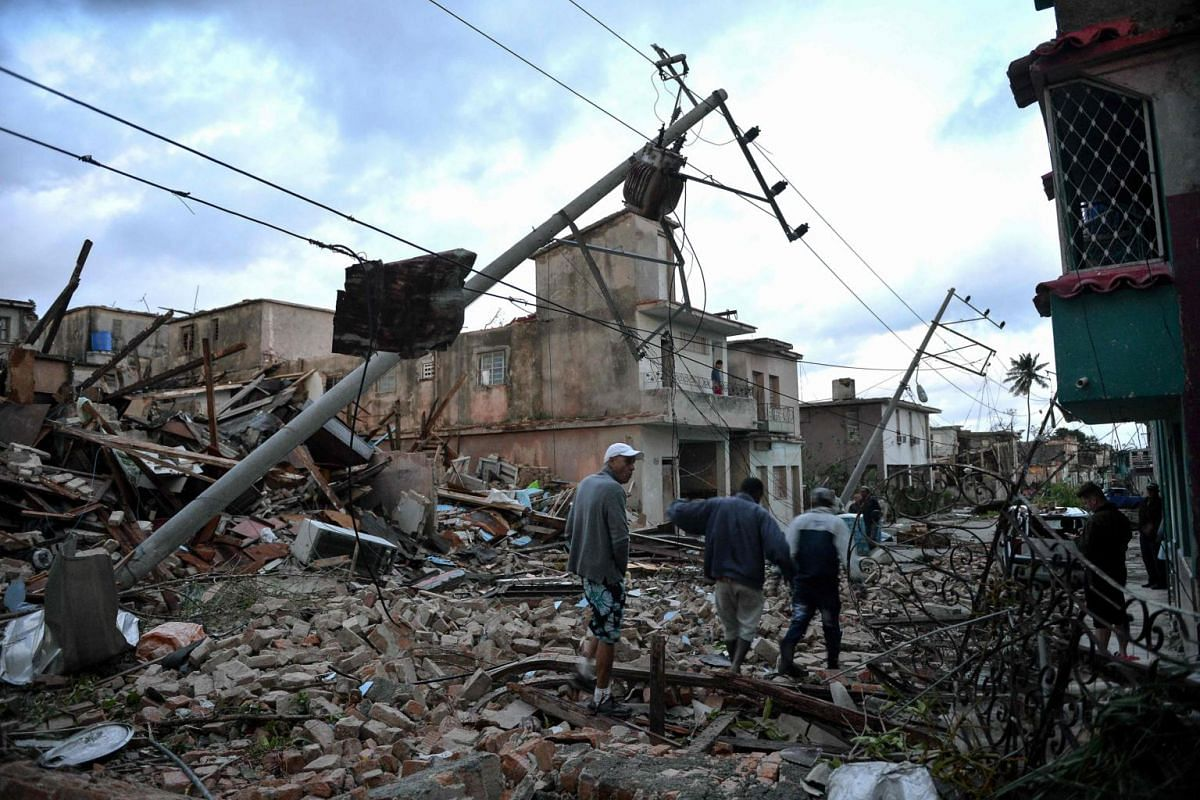 Residents walk amid the debris of buildings left after the passage of a tornado in Havana on Jan 28, 2019.