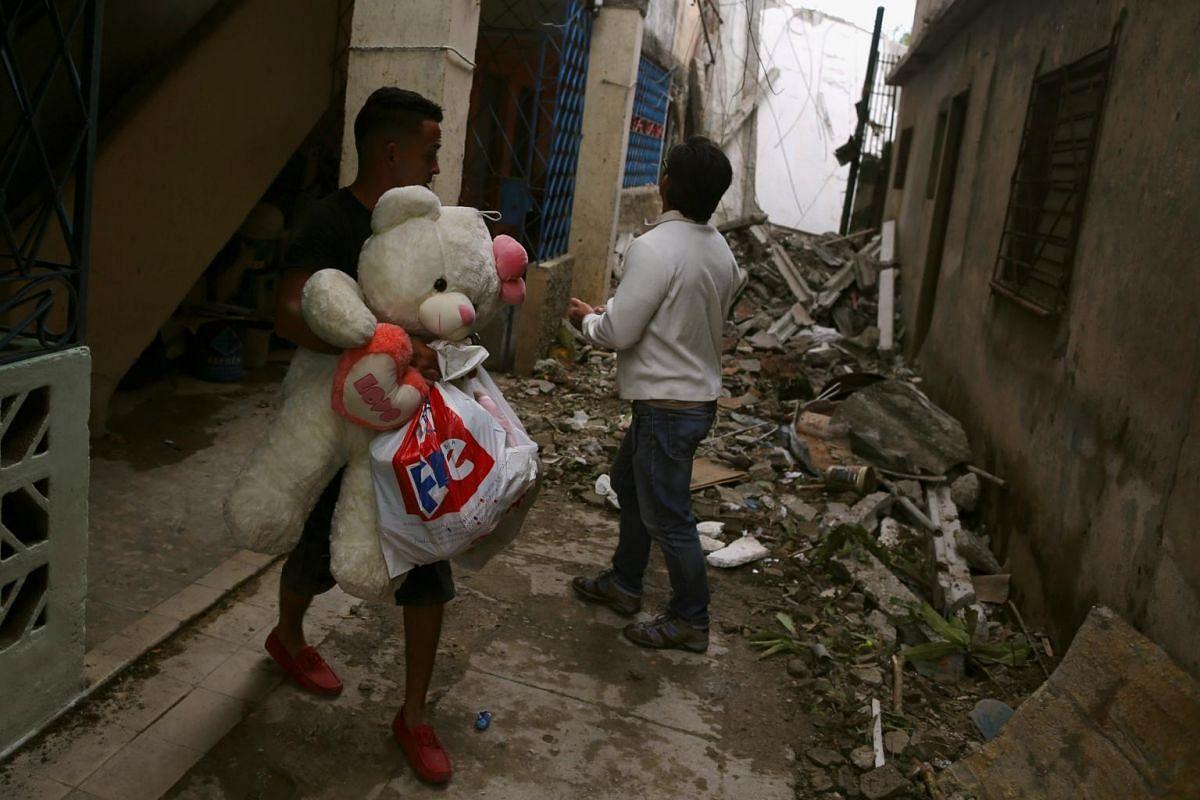 A man carries his belongings among debris after a tornado ripped through a neighbourhood in Havana, Cuba on Jan 28, 2019.