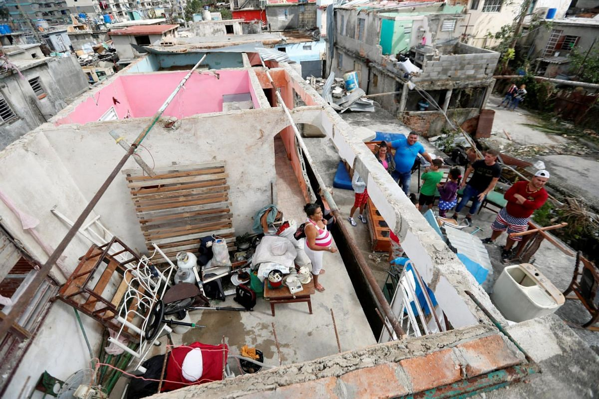 Several people chat in front of a roofless house in the municipality of Luyano in Havana, Cuba on 28 Jan, 2019 after a tornado hit.