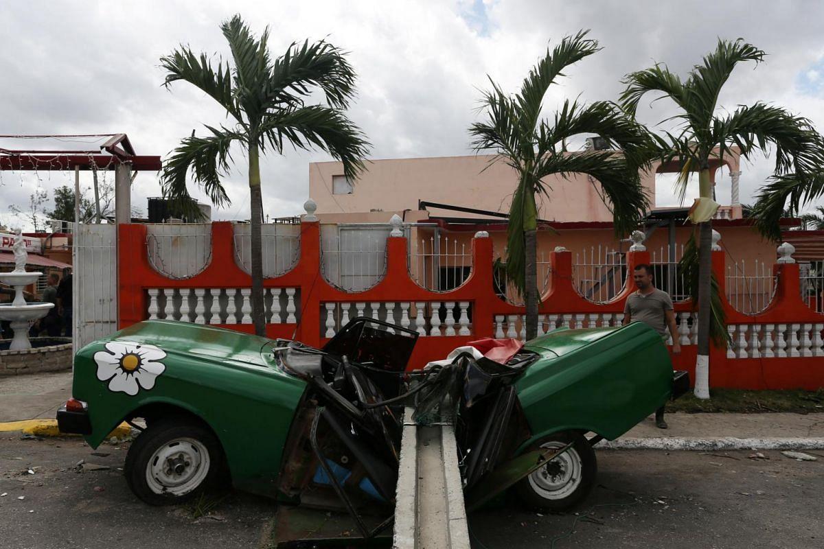 A man looks at a car hit by a post after a tornado ripped through a neighbourhood in Havana, Cuba, on Jan 28, 2019.