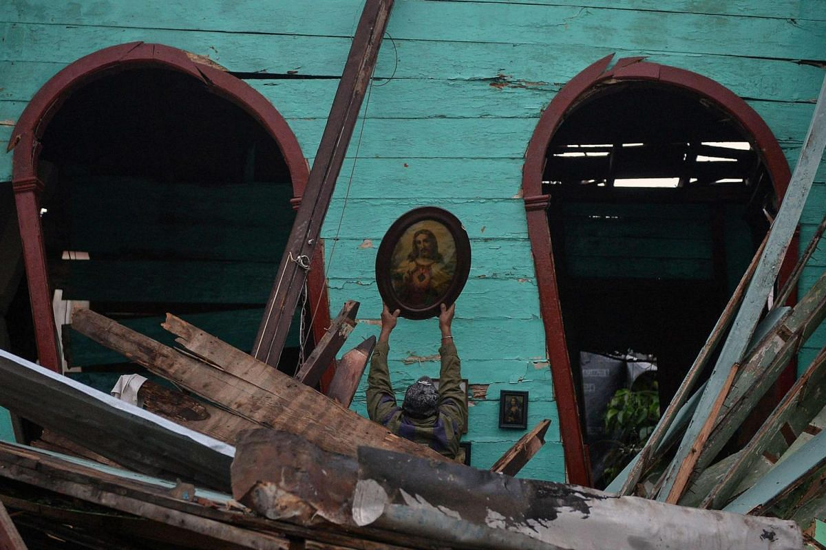 A man salvages an image of Jesus Christ from a destroyed building, after the passage of a tornado in Havana on Jan 28, 2019.