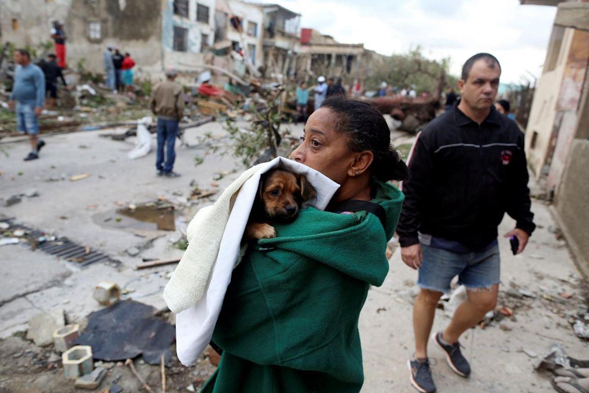 A woman holds her dog after a tornado ripped through a neighbourhood in Havana, Cuba on Jan 28, 2019.