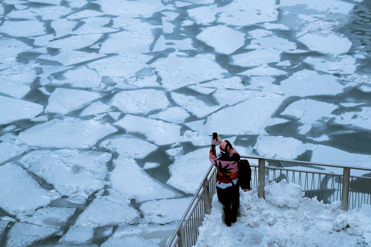 A pedestrian stops to take a photo by Chicago River, as bitter cold phenomenon called the polar vortex has descended on much of the central and eastern United States, in Chicago, Illinois, U.S., January 29, 2019. PHOTO: REUTERS