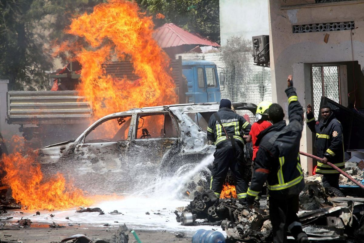 Somali firemen try to extinguish burning cars at the scene where a car bomb exploded in front of a restaurant in Mogadishu, Somalia January 29, 2019. PHOTO: REUTERS