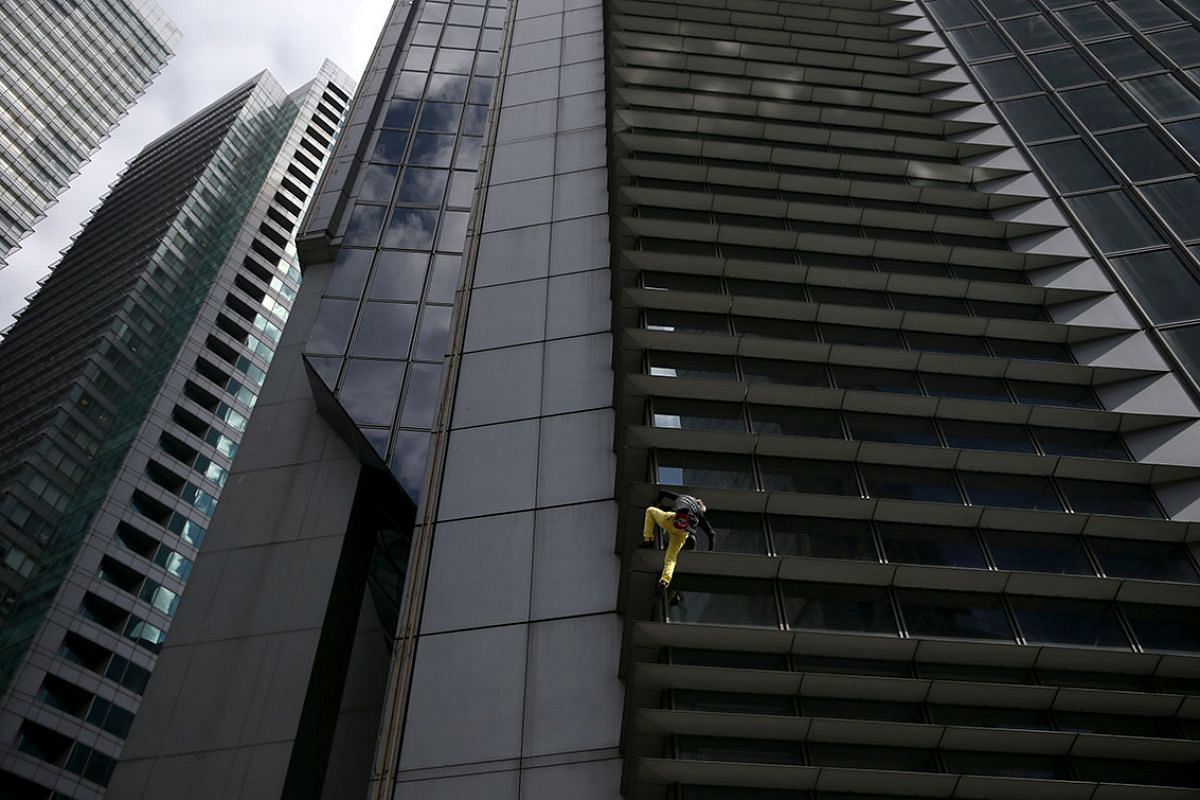 """French climber Alain Robert, also known as """"The French Spiderman"""", scales the 47-storey GT International Tower in Makati City, Metro Manila, Philippines January 29, 2019. PHOTO: REUTERS"""