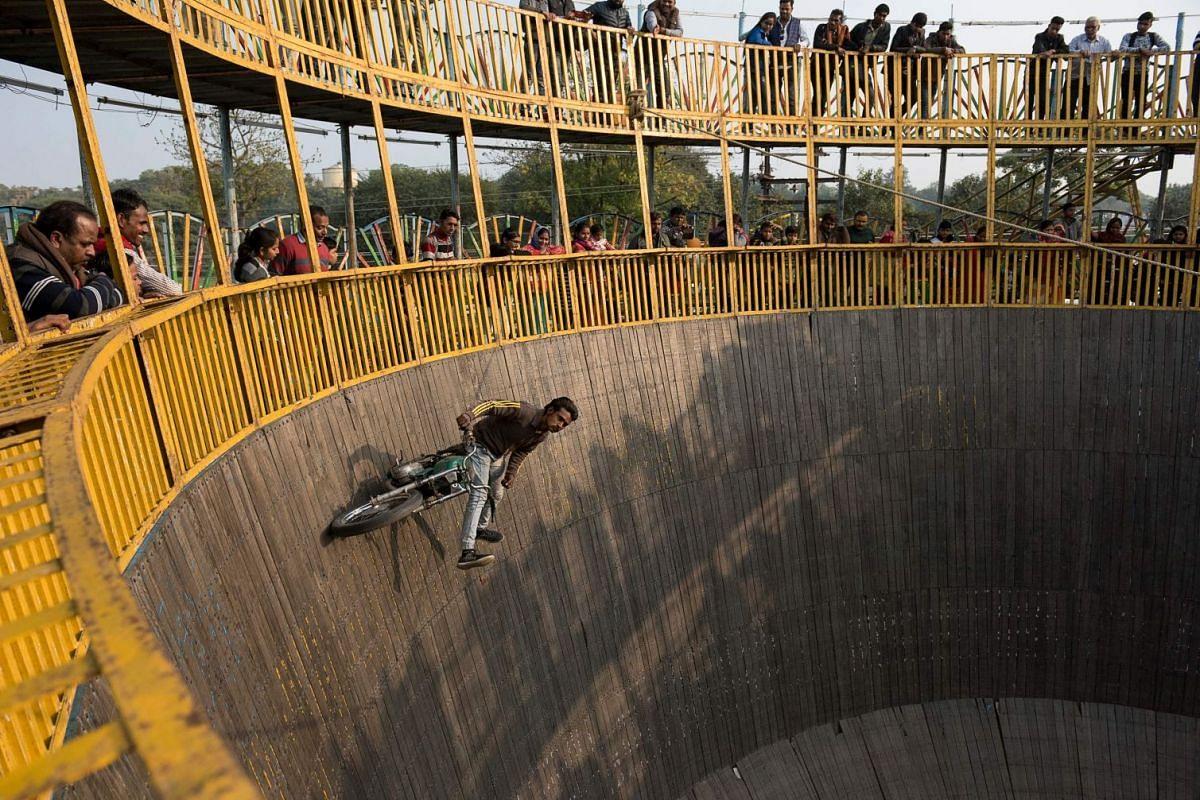 """A photo released on January 29, 2019 shows an Indian rider performing a stunt on a motorbike at a """"Wall of Death"""" motordrome carnival show at a fairground during the Kumbh Mela festival in Allahabad in India's Uttar Pradesh state on January 27, 2019"""