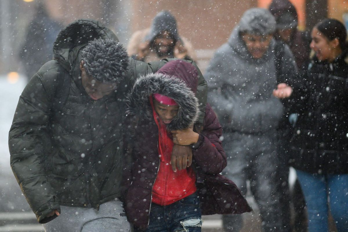 Pedestrians cross a street during heavy snowfall in downtown Manhattan on Jan 30, 2019, in New York City.  PHOTO: AFP