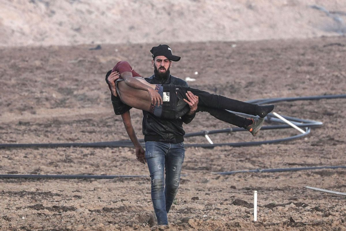 A Palestinian protester carries a wounded comrade during the clashes near the maritime border between Israel and Gaza Strip, Jan 29, 2019. PHOTO: EPA-EFE