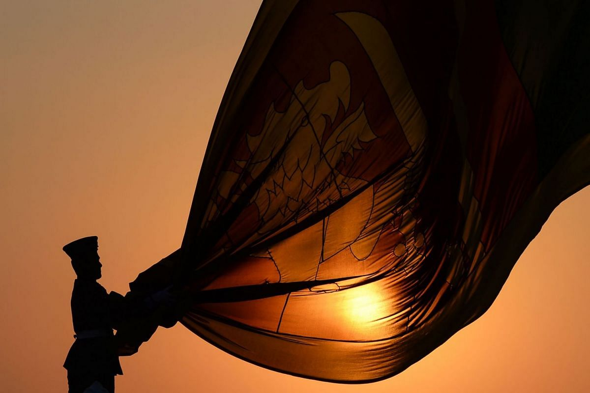 Sri Lankan Air force officers hold the national flag while it is lowered as part of a daily ceremony during sunset at the Galle Face Green promenade in Colombo on Jan 30, 2019. PHOTO: AFP