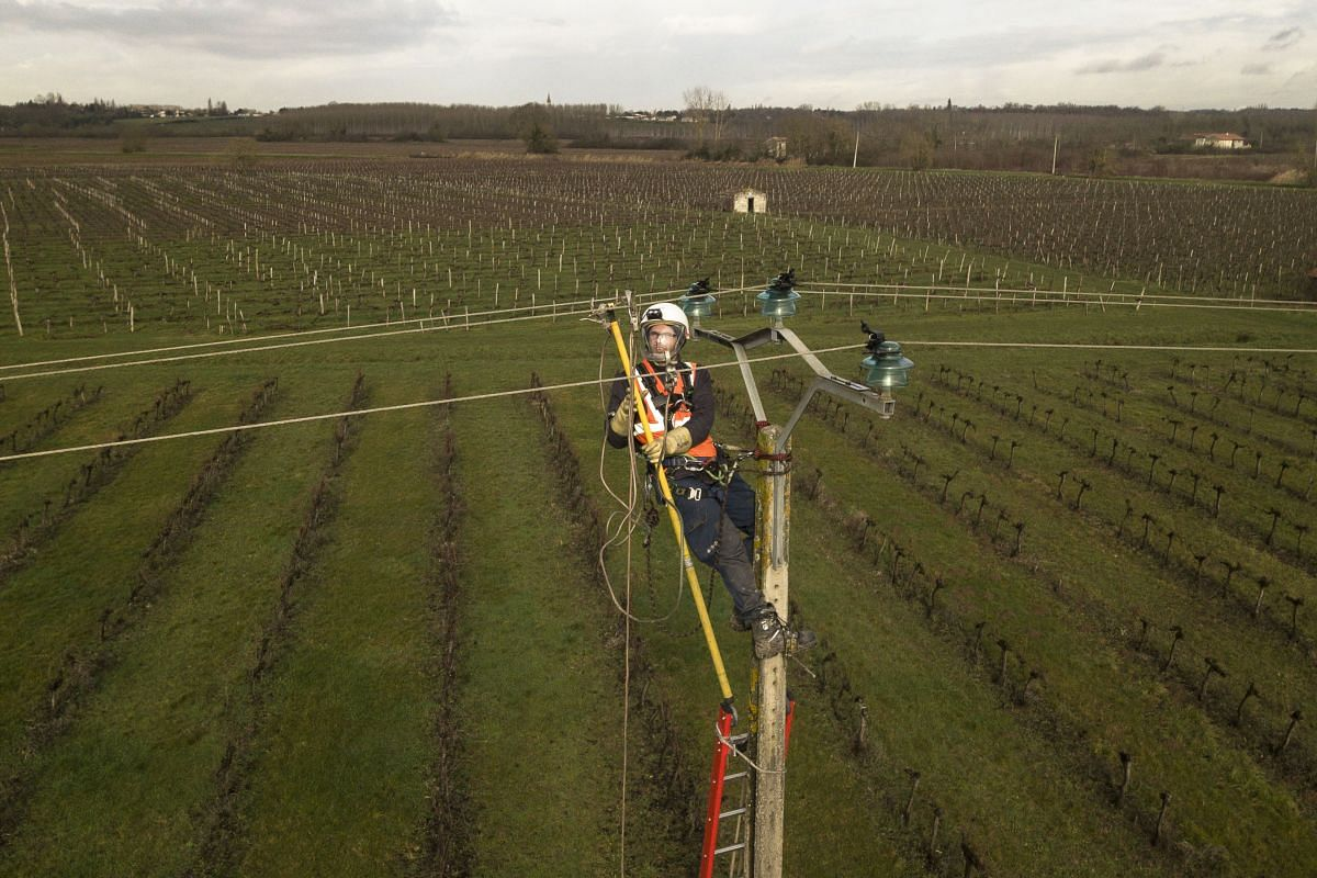 An aerial view shows a technician of French national electricity grid company Enedis repairing high-voltage cables in Lugon-et-l'Ile-du-Carnay, southwestern France, on Jan 30, 2019, after Storm Gabriel hit France overnight. PHOTO: AFP