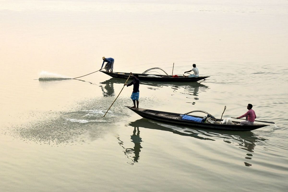 Indian fishermen slap water with sticks to lead fish into the nets in Brahmaputra River at sunset in Guwahati, Assam, on Jan 30, 2019. PHOTO: AFP