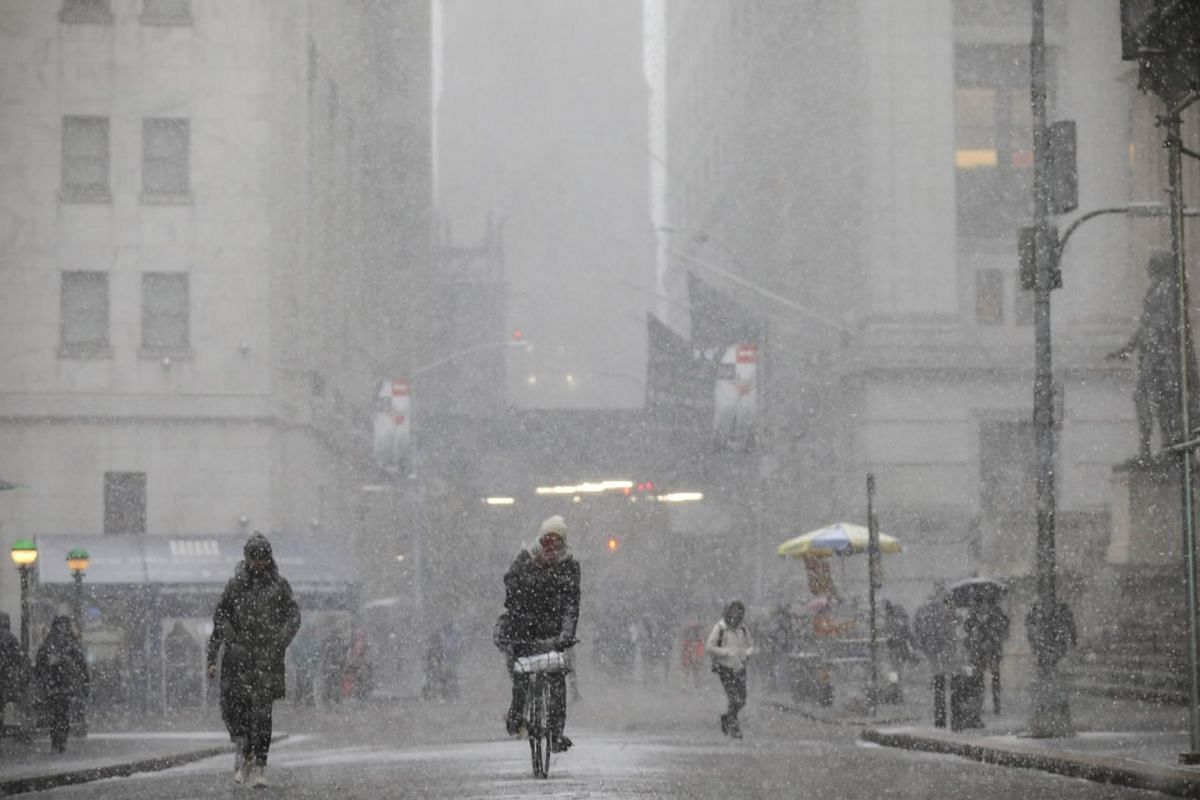 A cyclist rides through the falling snow in the Financial District, on Jan 30, 2019 in New York City.