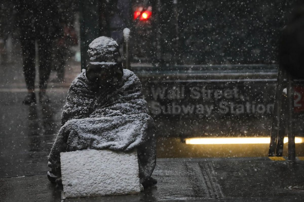 A homeless man sits in the falling snow in the Financial District, on Jan 30, 2019 in New York City.