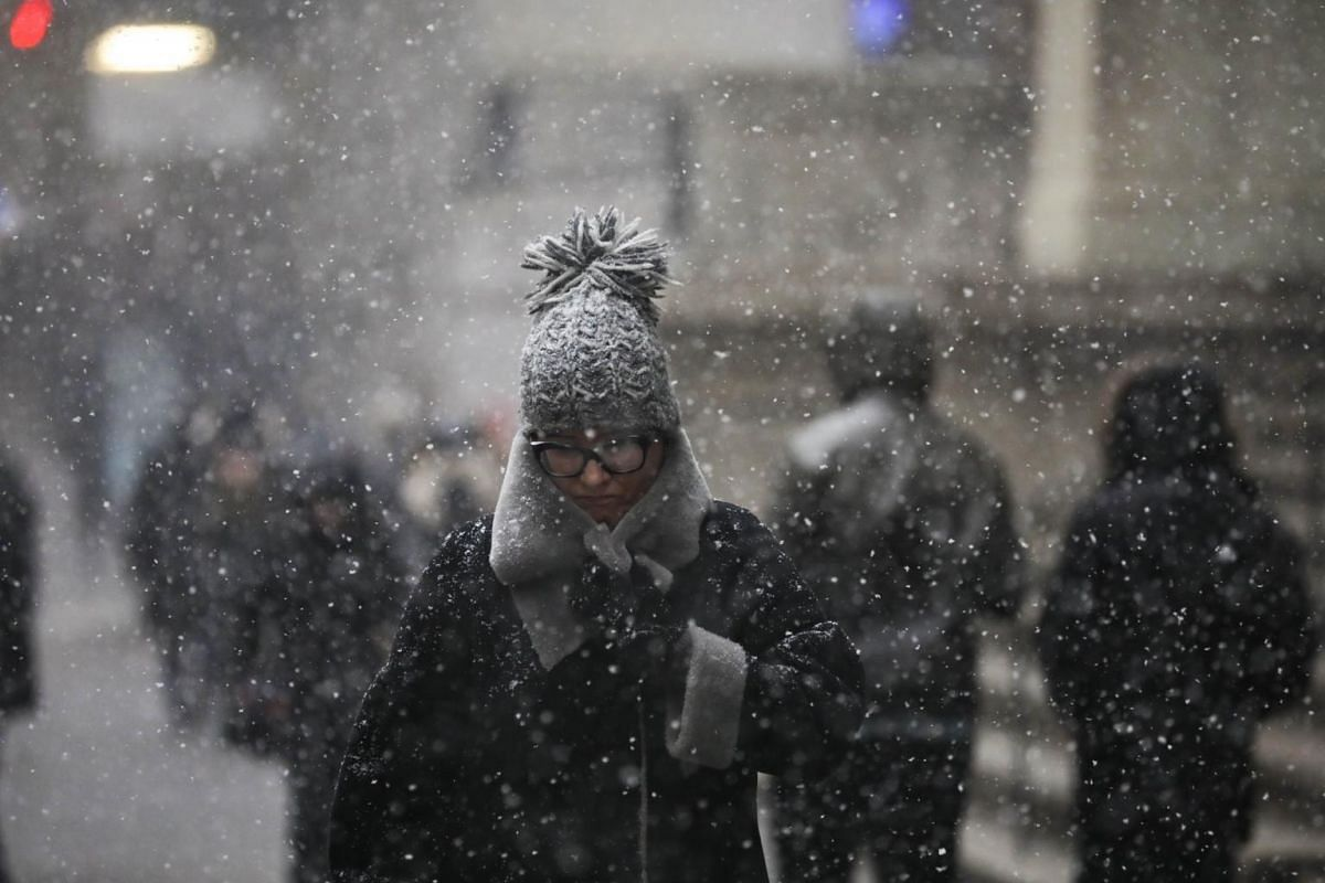 Pedestrians walk through the falling snow in the Financial District, on Jan 30, 2019 in New York City.