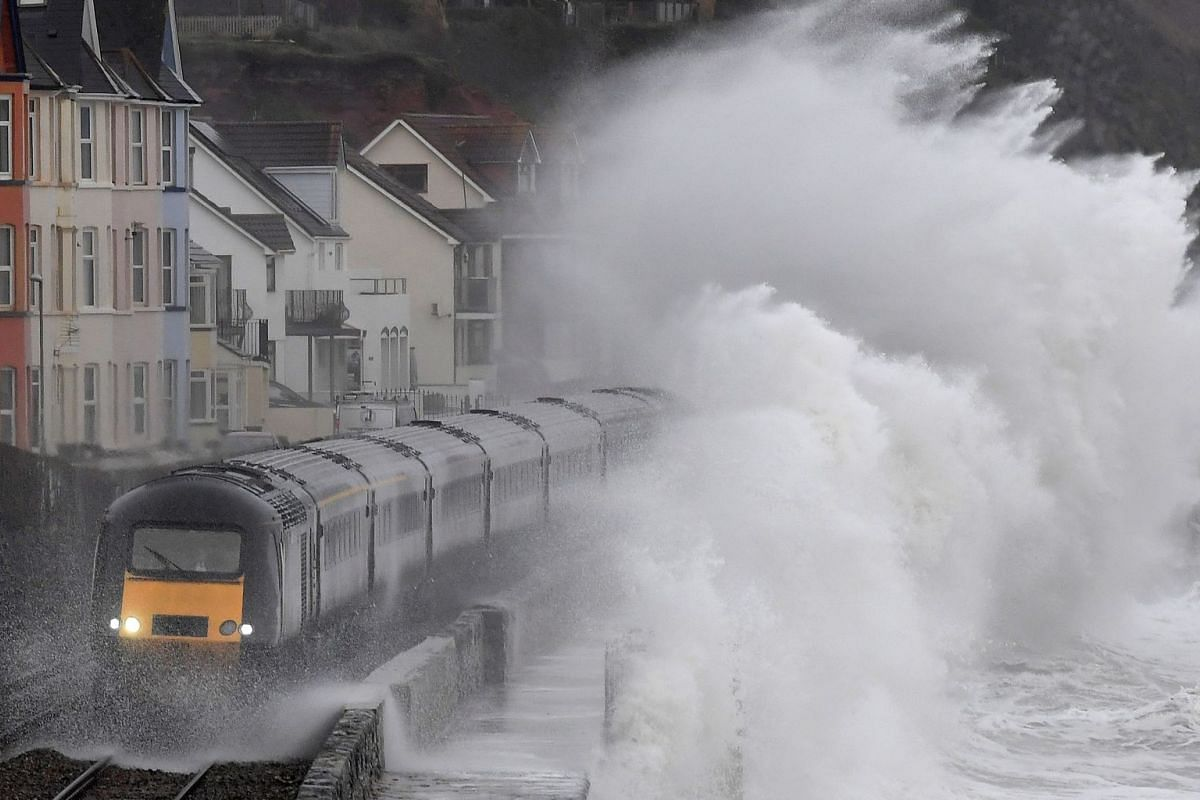 Large waves crash over a train as it passes through Dawlish in southwest Britain, January 31, 2019. PHOTO: REUTERS
