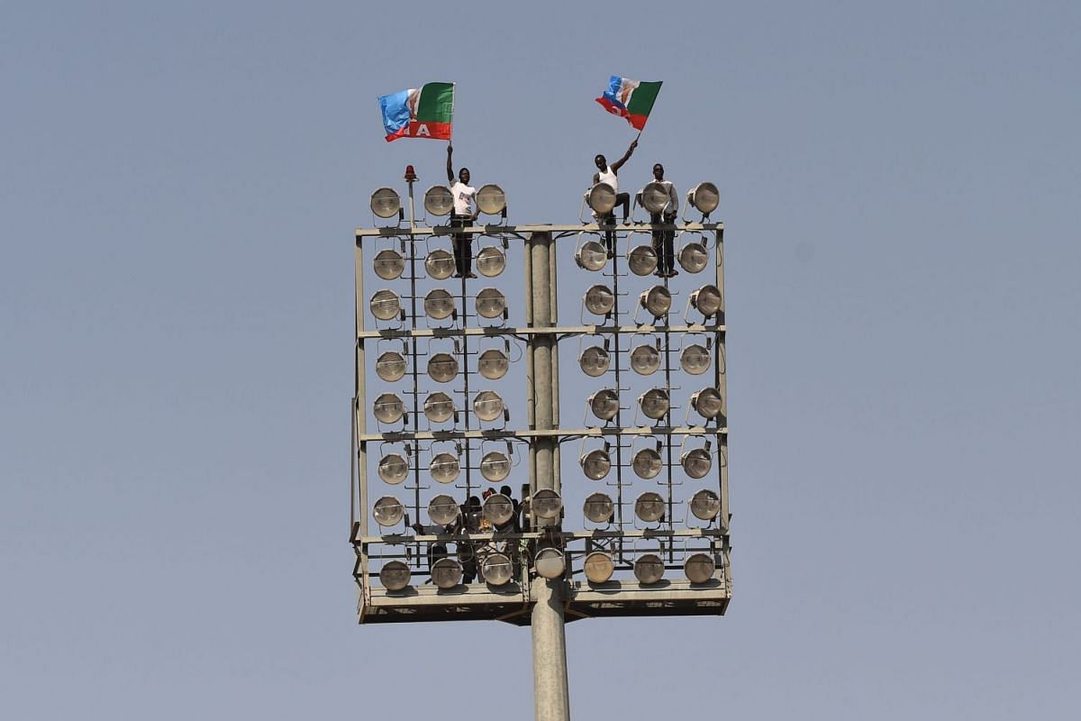 Supporters climbed on spots wave flags of the ruling All Progressives Congress (APC) during incumbent President Mohammadu Buhari's presidential campaign rally at the Sanni Abacha Stadium in Kano, on January 31, 2019. PHOTO: AFP