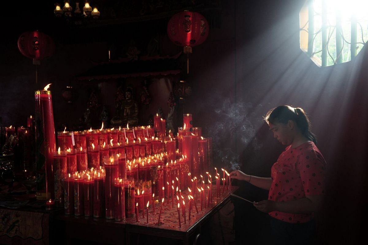 A woman lights candles as she prays during celebrations of the Chinese Lunar New Year at a temple in Jambi, Indonesia, on Feb 5, 2019.