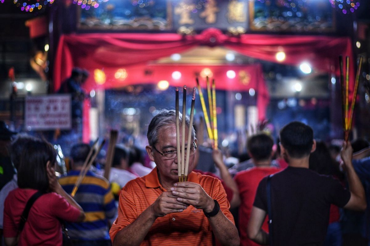 Devotees rushing to plant the first joss stick of the Lunar New Year of the Pig at the stroke of midnight at the Kwan Im Thong Hood Cho temple.