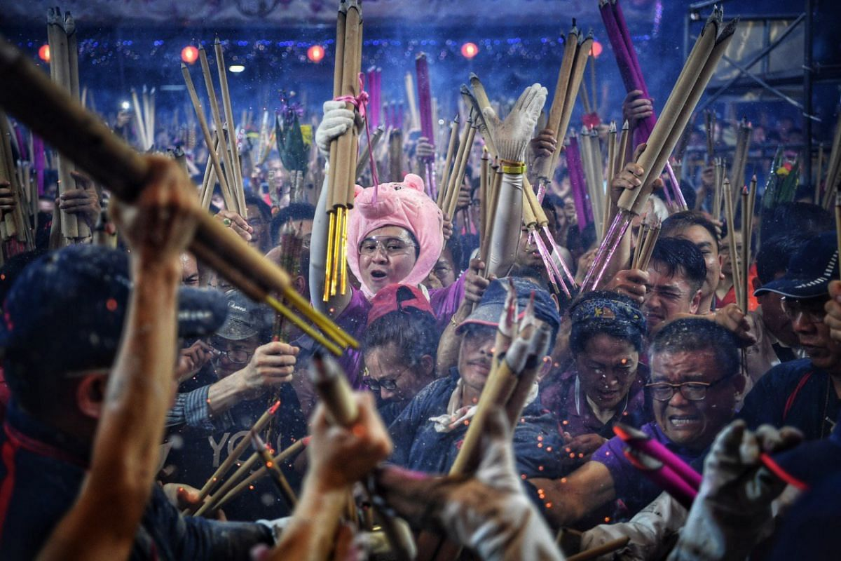 Devotees rushing to plant the first joss stick of the Chinese New Year of the Pig at the stroke of midnight at the Kwan Im Thong Hood Cho temple.