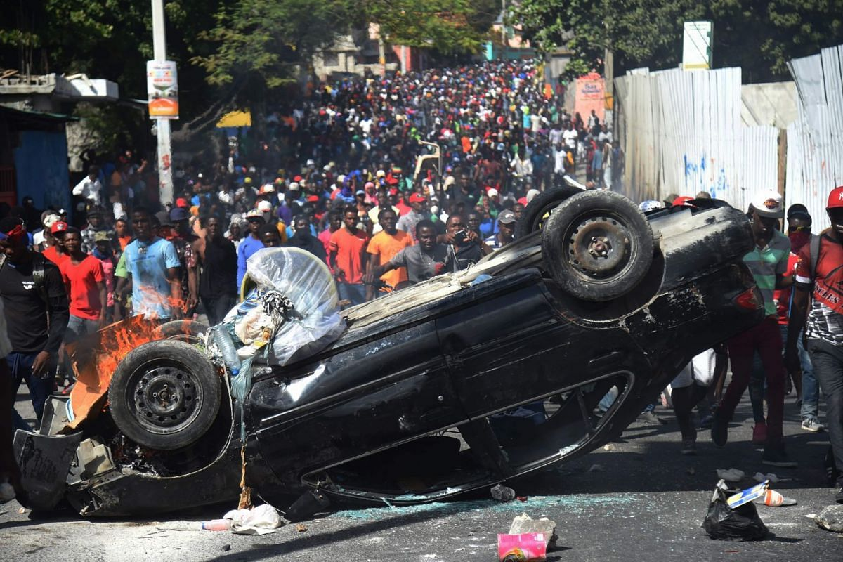 A car is placed as a barricade by demonstrators during clashes in the center of Haitian capital Port-au-Prince on February 12, 2019, as a sixth day of protests against Haitian President Jovenel Moise and the misuse of Petrocaribe funds continued. PHO