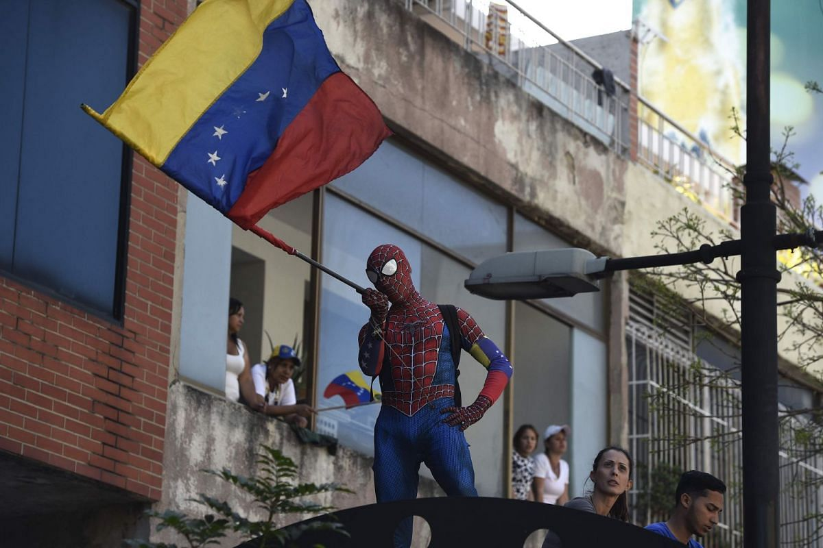 A supporter of Venezuelan opposition leader and self declared acting president Juan Guaido, dressed in a Spider-Man costume, waves a national flag during a rally to press the military to let in US humanitarian aid, in eastern Caracas on February 12,