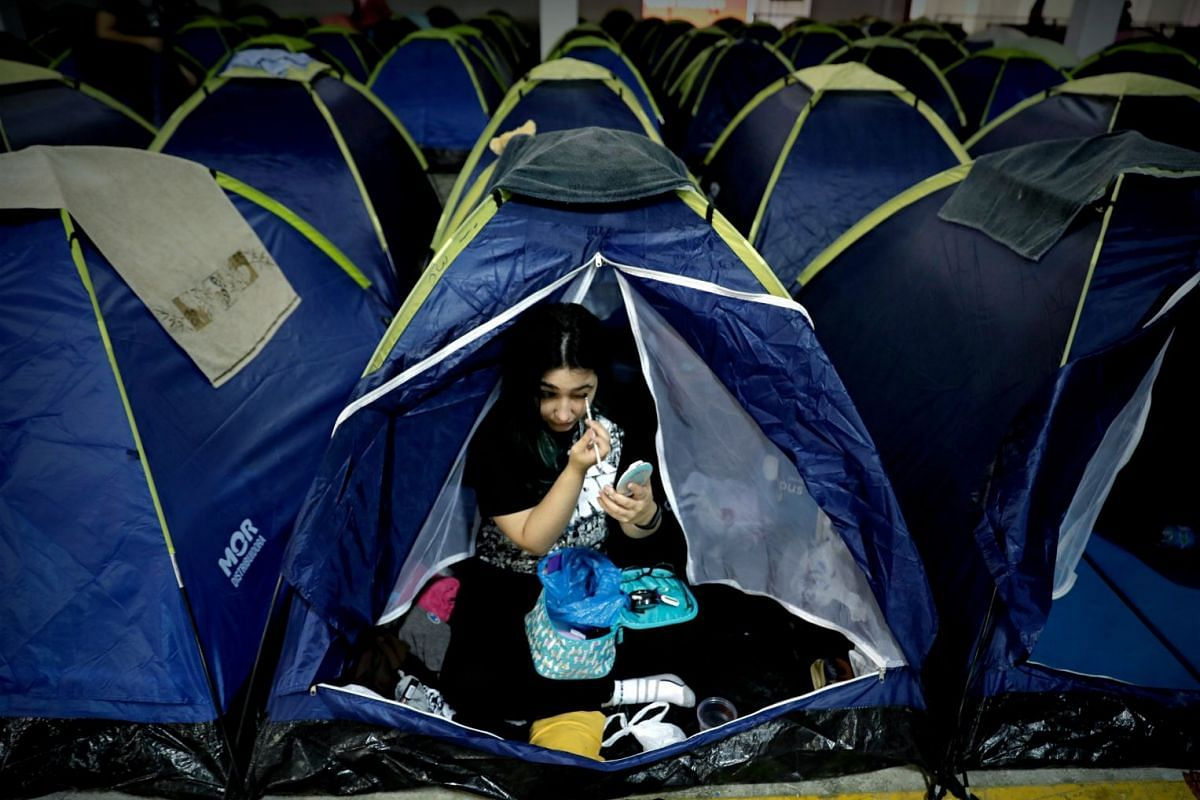 A woman adjusts her makeup in a tent at the camping area of the Campus Party, in Sao Paulo, Brazil, on Feb 12, 2019.