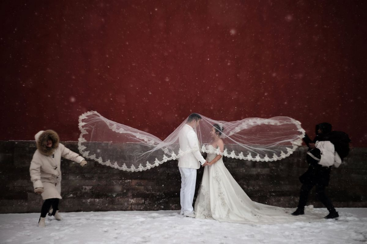 A couple poses for a wedding photo shoot amid snowfall at the Imperial Ancestral Temple in Beijing, China February 12, 2019. PHOTO: CHINA DAILY VIA REUTERS