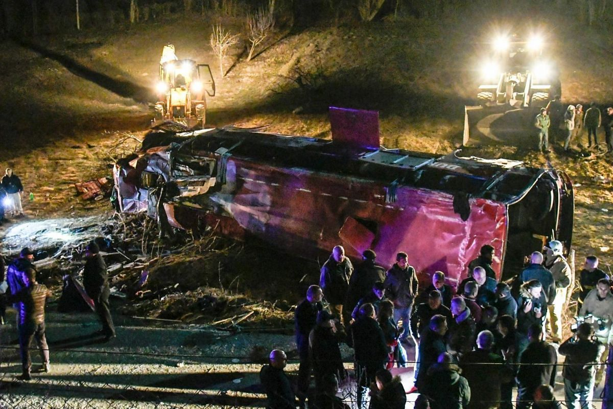 Bystanders and rescue personnel gather near the wreckage of a bus on a road near Skopje on February 13, 2019. PHOTO: AFP