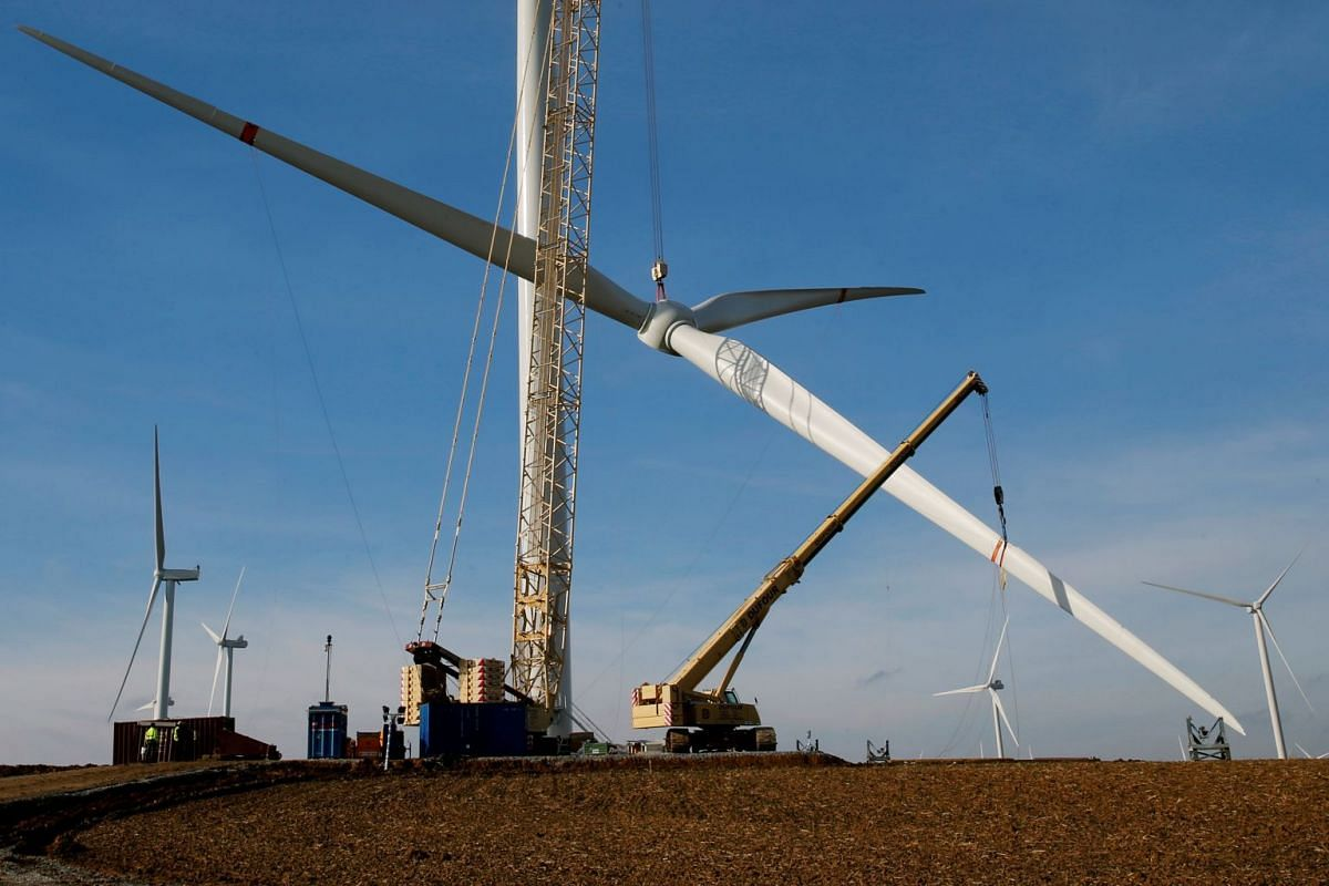 A crane lifts a propeller to the top of a power-generating windmill turbine in a wind farm in Graincourt-Les-Havrincourt, France February 13, 2019. PHOTO: REUTERS